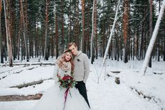 Stylish bride and groom with a bouquet are posing on background of the snowy forest. Winter wedding. Artwork Stock Photo