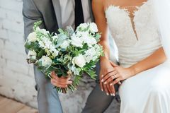 Stylish bride and groom are holding bridal bouquet stock photo