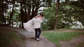 Stylish bride and groom in a park. Groom takes his bride in his arms and swirls around. Happy lovers share wedding day. stock footage