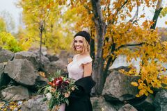 Stylish bride with a rustic bouquet is posing before a lake on the hill. Young blonde in a knitted hat with pompom and. With dreadlocks smiles. Autumn wedding Stock Photos