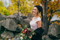 Stylish bride with a rustic bouquet is posing before a lake on the hill. Young blonde in a knitted hat with pompom and. With dreadlocks smiles. Autumn wedding Royalty Free Stock Photos