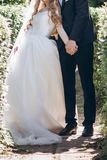 Stylish bride in silk dress and groom in suit hugging in sunny g Stock Image