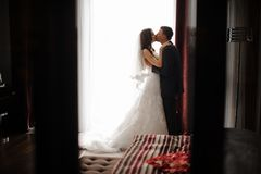 Bridegroom and bride in long dress are kissing near the window. Stylish bridegroom and charming brunette bride in long classic white dress are kissing near the royalty free stock images