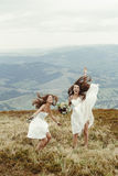 Stylish bridesmaid and gorgeous bride having fun and jumping, bo. Ho wedding, luxury ceremony at mountains stock images