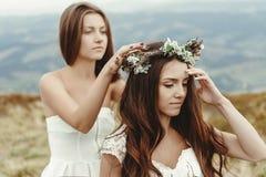 Stylish bridesmaid helping gorgeous bride preparing, boho wedding, luxury ceremony at mountains stock images