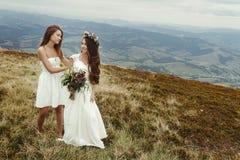 Stylish bridesmaid helping gorgeous bride preparing, boho weddin Stock Photos