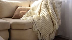 Stylish brightly interior of living room. Inviting comfortable sofa with handmade woolen blanket. Comfortable place for reading or relaxing in Scandinavian stock video