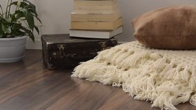 Stylish brightly part of living room with old vintage suitcase, books, potted plant and woolen handmade blanket on luxury wooden f. Loor. Comfortable place for stock video footage