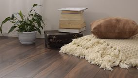 Stylish brightly part of living room with old vintage suitcase, books, potted plant and woolen handmade blanket on luxury wooden f. Loor. Comfortable place for stock video
