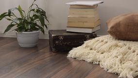 Stylish brightly part of living room with old vintage suitcase, books, potted plant and woolen handmade blanket on luxury wooden f. Loor. Comfortable place for stock footage