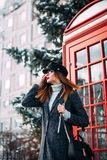Stylish British portrait of a charming young woman brunette in a fashionable cap walking down the street near the red phone booth. Expressing positive emotions Royalty Free Stock Image