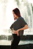 Stylish brown hair girl posing front of city fountain Royalty Free Stock Photos