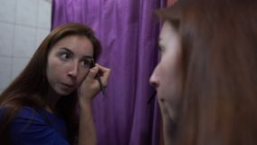 Stylish brown hair girl putting makeup on her face before a mirror in a room. Cheerful view of a young brown hair woman with straight long hair in a dark orange stock video footage