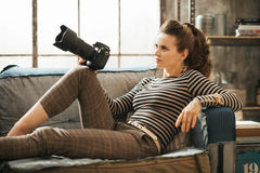 Stylish brown-haired female is sitting and holding dslr camera Stock Photos