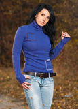 Stylish brunet. Pretty young brunet in blue sweater at fall season park alley Stock Photo