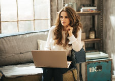 Stylish brunet woman sitting on couch and working on laptop Royalty Free Stock Image