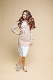 Stylish brunette in beige dress with hand on waist. Royalty Free Stock Photography