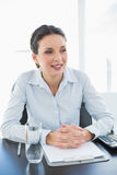 Stylish brunette businesswoman joining her hands and looking away Stock Images