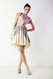 Stylish brunette female in fashion dress standing Stock Photography