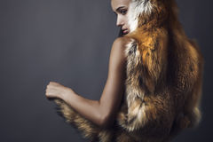 Stylish brunette in the fox cape. Royalty Free Stock Photography
