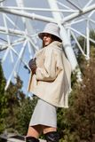 Stylish brunette girl dressed in beige short sheepskin coat, gray gloves and little hat poses outside on the sunny day royalty free stock photography
