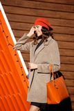 Stylish brunette girl dressed in a light brown coat and orange beret posing against the background of bright orange royalty free stock images