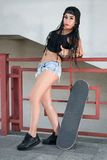 Stylish brunette girl with glasses shorts and a cap is standing Stock Photo