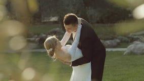 Stylish brunette groom tilts his slender bride and stock footage