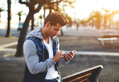 Stylish brunette hipster using cell phone at sunny evening. Portrait of handsome young man sending a text message while standing outside, male student reading Stock Image