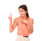 Stylish brunette lady making a victory sign Royalty Free Stock Images