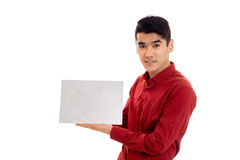 Stylish brunette male model in red shirt posing with empty placard isolated on white background Royalty Free Stock Images