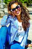 Stylish brunette model in hipster clothes outdoors Stock Photos