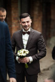 Stylish brunette smiling groom in a suit with a brown bow holds Royalty Free Stock Images