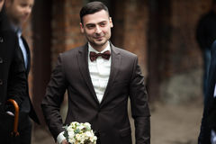 Stylish brunette smiling groom in a suit with a brown bow holds Royalty Free Stock Image