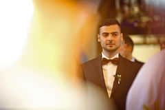 Stylish brunette smiling groom in a suit with a brown bow holds Stock Image