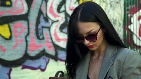 Portrait of gorgeous brunette against graffiti wall. Stylish brunette in sunglasses and with red lipstick is posing for camera against graffiti wall. Fashionable stock video footage