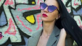 Stylish brunette in sunglasses straighten her hair in slow motion. Stylish brunette in sunglasses and with red lipstick is posing for camera against graffiti stock video footage