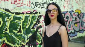 Beautiful brunette in sunglasses walking in slow motion against graffiti wall. Stylish brunette in sunglasses and with red lipstick is posing for camera against stock video