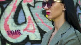 Stylish brunette in sunglassses posing for camera at background of graffiti wall. Stylish brunette in sunglasses and with red lipstick is posing for camera stock video footage