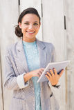 Stylish brunette using tablet pc Royalty Free Stock Photography