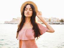 Stylish brunette woman enjoying sunrise on seafront. Beautiful brunette young woman wearing pink dress and straw hat enjoying sunrise on seafront in old european stock images
