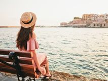 Stylish brunette woman enjoying sunrise on seafront. Beautiful brunette young woman wearing pink dress and straw hat enjoying sunrise on seafront in old european Stock Photography