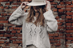 Free Stylish Brunette Woman In White Hat And Boho White Sweater Posing Near Red Brick Wall Royalty Free Stock Images - 89971519