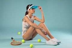 Fashion brunette female model sitting with tennis racquet royalty free stock photos