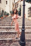Stylish brunette woman walking in old town. Beautiful brunette young woman wearing pink dress and straw hat walking on the street in old european Town. Fashion Royalty Free Stock Images