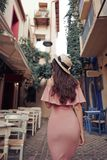 Stylish brunette woman walking in old town. Beautiful brunette young woman wearing pink dress and straw hat walking on the street in old european Town. Fashion Royalty Free Stock Photos