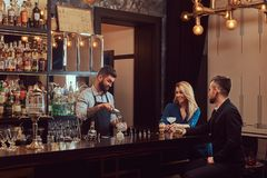 Stylish brutal barman serves an attractive couple who spend an evening on a date. Royalty Free Stock Images