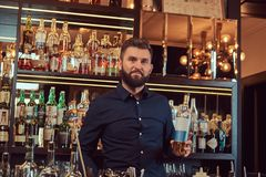 Stylish brutal bartender in a black shirt presents a bottle of exclusive alcohol at bar counter background. Royalty Free Stock Photography