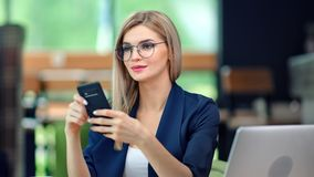 Stylish business female typing message looking at screen of smartphone having positive emotion. Stylish blonde business female typing message looking at screen stock video