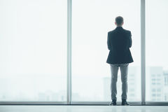 Stylish business man in the background of a large window in office Royalty Free Stock Photos